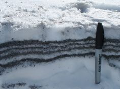 Alternating ash and snow fall over several days create layers in this examination of tephra-fall deposits (volcanic ash) from the initial explosions from Redoubt volcano on March 22 and 23, 2009.