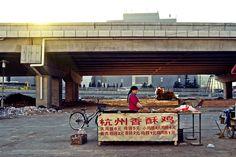Woman Selling Fried Bread Under a Bridge