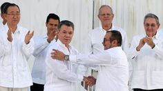 """Colombian President Juan Manuel Santos and rebel leader Rodrigo Londono, aka Timoleon """"Timochenko"""" Jimenez, shake hands as they sign a historic peace treaty between the government and the Revolutionary Armed Forces of Colombia (FARC) in Cartagena, Colombia. © Luis Acosta"""