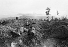 The bodies of U.S. Marines lie half buried on Hill 689, about 2 1/2 miles west of Khe Sanh, in April of 1968. Fellow Marines stand guard in the background after battling entrenched North Vietnamese troops for the hill.
