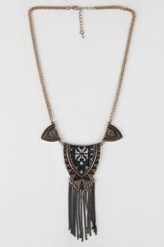 This tribal necklace features engraved patterns , a shield shape with fabric outlined with beads, and long metallic curb link fringe. The curb link chain has an adjustable lobster hook closure. Measur