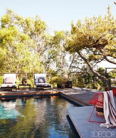 Outdoor lounge area beside pool in forested setting