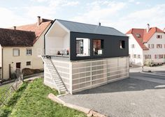 This black house by German studios Fabian Evers Architecture and Wezel Architektur is raised up over a translucent base where the client's truck can be stored
