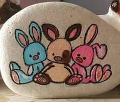 Three colorful bunnies painted rock