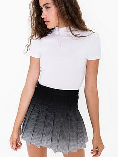 A gabardine mini skirt with a high waist, side button/zipper closure and pleats. In assorted prints.