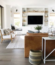 neutral living room with leather couch and shelves around tv