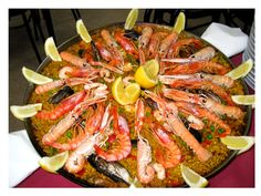 """Paella is a Valencian rice dish that originated in its modern form in the mid-19th century near lake Albufera, a lagoon in Valencia, on the east coast of Spain"""