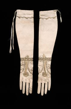 Pair of women's gloves early 19th century Cream colored satin embroidered with gold thread and spangles. Peacock feathers worked on back of each glove with band around each wrist of neutral blue satin cut out, appliquéd, and embroidered with gold thread. Small feathers and foliage embroidered with gold on cuffs with remains of silk ribbons drawn through cuffs.
