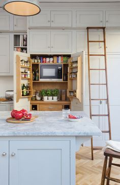Charlie kingham West London Victorian Town House | A hardwood shaker style kitchen in located in the west of London. Integrated larder unit with a built in Miele microwave and mounted spice racks.