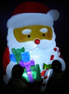 """Light up any room with this Christmas light night.  This iconic Santa Claus is perfect for the holidays.  He stands about 6 ½"""" tall and is holding a candy cane and wrapped presents for good little girls and boys.  He is a real cutie. He requires 3 AA batteries, which are not included.  Check out my eBay auctions."""