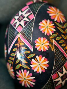 Ring-Around-The-Rosy Pysanky Egg: A Garland of Pink, Yellow and White Blooms Encircles Traditional Scarves on Black Background