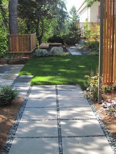 Inexpensive landscape drama with square concrete stepping stones trimmed with pebbles...