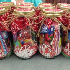 Easy and cheap gift idea. Mason jars filled with candy and toys from the dollar store. Put some fabric under the ring and tighten.