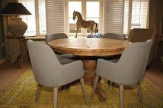 Ronde eettafel van teak hout met moderne eetkamer fauteuiltjes