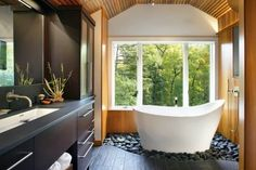 Stand alone tub nestled in black rocks in the corner of a spa like master bath.  So luxurious.