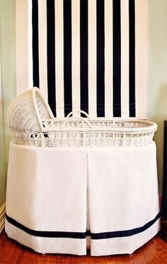 Simple black & white bassinet and the striped DIY Roman shade provide quiet neutrality.