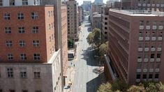 Ad: An aerial view of an empty street lined by tall buildings in Johannesburg city centre, during the covid-19 coronavirus lockdown. Johannesburg City, Aerial View, Stock Footage, Empty, Transportation, Centre, Buildings, Campaign, Street