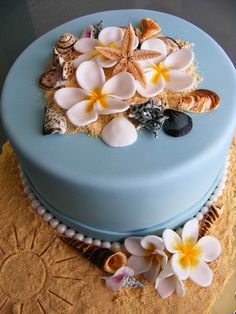 Blue cake with sea shells, pearls and plumerias.