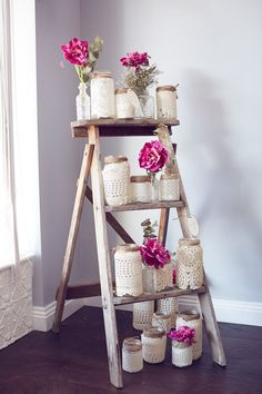 LOVE this wedding decor idea! Twine and crochet wrapped mason jars stacked on a ladder alongside pretty blooms in cut glass jars.
