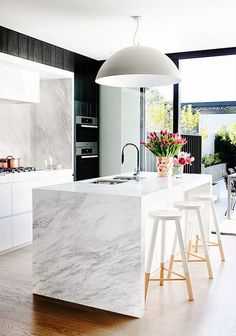 Marble kitchen with modern light fixture, beautiful flowers, and wood bar stools: