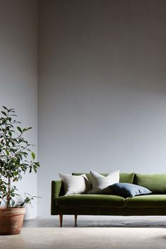 My next sofa will be a velvet one. Love this sofa by Swoon. Green velvet sofa with beige and blue cushions.