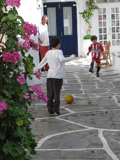 Playing soccer on the winding paths. Mykonos, Greece