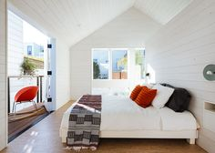 In this master bedroom, the gable roof and balcony create the illusion of generous space. A free-standing wall  behind the bed divides the sleeping space from the bathroom.