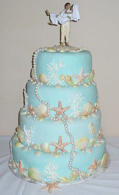 Beach theme wedding cake  This cake is decorated with white chocolate shells dusted with pearl dust in different colors, coral made of royal icing, and pearls individually made from fondant and dusted in pearl dust.  Tiers covered in aqua tinted fondant.