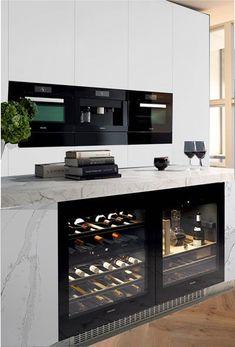 White marble kitchen island with wine fridges. The other one should be a  beer fridge. Black appliances, white doors, medium dark hard wood floor.