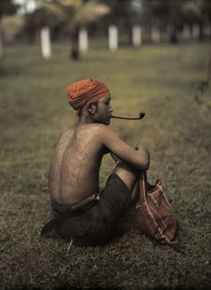 Kahme man displays tattooed back; Northeastern Siam. photo by W. Robert Moore