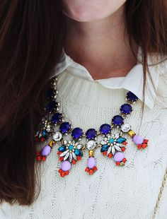 cute colorful necklace over the white sweater & white shirt