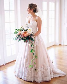 Obsessed with this lush Bridal Bouquet of Blush, Ivory, and Greenery. The large roses against her Blush Morilee by Madeline Gardner Wedding Dress, style 2674, look classic and elegant with the cascading greenery. Photo by Katie Grant Photography.
