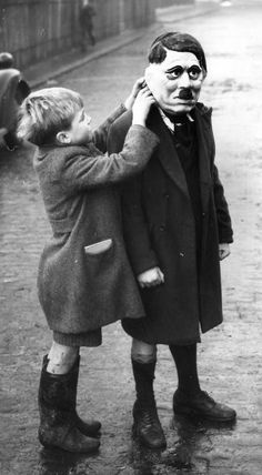 A young boy adjusts his friend's Adolf Hitler mask during a game on a street in King's Cross, London, 1938. Photo by William Vanderson