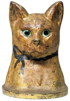"""A Rare Painted Cast-Iron Cat Doorstop with Glass Eyes    American, circa 1900. this small, but powerful, wide-eyed cat transcends into a piece of American folk art as well as being a functional doorstop. Height 6½"""", width 5"""". Provenance: Kim Lane, Middlebury, Vermont."""