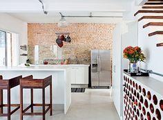 """O morador Phil Chaves transformou a casa de vila em um galpão de Nova York. """"Queria espaço amplo e uma cozinha que se relacionasse com toda a casa"""", diz. O ambiente, projetado pela arquiteta Rachel Nakata, tem adega de tijolos cilíndricos de cerâmica (Foto: Lufe Gomes/Casa e Jardim)"""