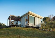 10 Prefabricated or Modular Structures That Use Plywood in Creative Ways - Photo 1 of 11 - A compact prefab vacation home in the seaside community of Onemana Beach in New Zealand is clad in plywood and vertical timber battens finished in Resene's Lumbersider paint in Foam.