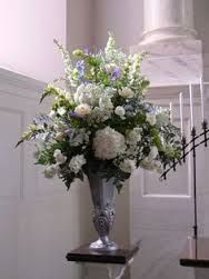 white flowers (hydrangeas, delphiniums, roses, carnations) with some pale blue, in a silver urn