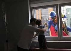 A man dressed as Superman smiles at patient Joao Bertola, 2, and his father at the Hospital Infantil Sabara in Sao Paulo, Brazil.