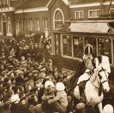 Haarlem (Nederland) Op het stationsplein in Haarlem rijdt Sinterklaas op zijn witte paard. De Sint is gekleed met mijter en baard en heeft een rode mantel aan. Veel ouders met kinderen zijn  gekomen om de Sint te zien. Op de achtergrond is de fabriekshal van Beynes. De Sint op zijn paard  rijdt langs de tram. november 1922. LET OP! Dit is een minimaal bewerkt lowres bestand van een origineel dat een raster bevat. Wilt u een groter en/of bewerkt bestand neem dan contact op met 070-3314160 of…