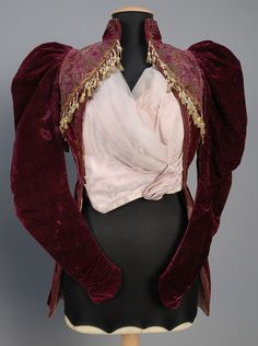 VELVET JACKETS, 1880s and 1890s. One deep red dolman with red and gold floral silk damask trimmed in printed cotton and ecru lace with beaded tassels. One amethyst having gigot sleeve, lavishly embroidered yoke in silk and metallic thread with beaded tassels, moire faille insert. Front