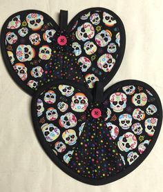Sugar skull themed hot pad pair with colorful sugar schools on a black background. A personal favorite from my Etsy shop https://www.etsy.com/listing/228109235/colorful-sugar-skull-heart-hot-pad-pair Day of the dead All souls day Calavera