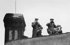 East German border guards watch the Queen through binoculars during her visit to the Berlin Wall