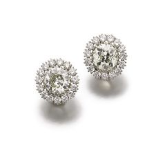Pair of diamond ear clips Each set with a circular-cut diamond weighing 3.32 and 3.79 carats respectively, framed with brilliant-cut diamonds