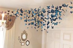 DIY swarm of butterflies. Made by hanging hand cut butterflies from ceiling with fishing wire and white eye hooks.