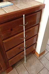 Tension rod pressed up against drawers to keep children out