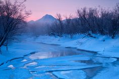 Very frosty morning on the river Paratunka. On a background a volcano Viluchinsky.  Kamchatka, Siberia, Russia.