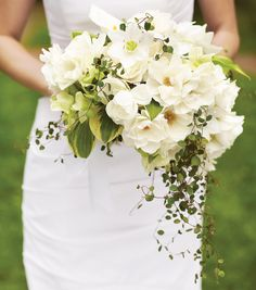Brides.com: Wedding Flower Bouquet Shapes. Asymmetrical. Instead of forcing flowers into an unnatural shape, this bouquet allows for a more fluid, organic arrangement in which the blossoms and foliage are longer and more abundant on one side than the other.  Bouquet of garden snow roses, mini hosta leaves, hellebores, Eucharist lilies, calla lilies, and wire vine by Bridget Vizoso of The Designers' Co-Op.  Gown, David's Bridal