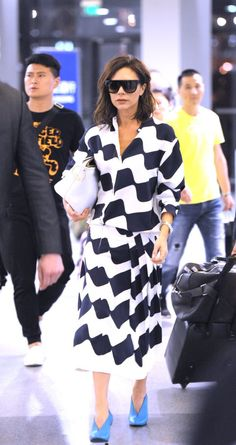 Victoria Beckham arrives at the airport in Shanghai, China wearing a stripey co-ord dress with bright blue shoes, May 2017