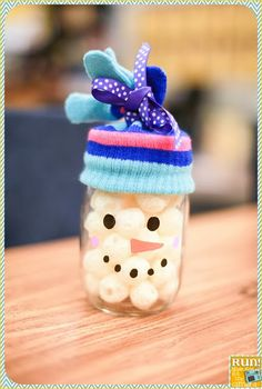Using a mason jar, a glove, paint pens, and cheese balls to make this cute snowman! (Or marshmallows!)