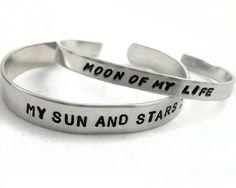 "The perfect set for a Khal and his Khaleesi, this set consists of a 3/8"" man's bracelet stamped with 'my sun and stars', and a narrow woman's bracelet stamped with 'moon of my life'. These are shown in my Handwriting Caps and Large Arial fonts.They are made from pure, hypoallergenic aluminum.  A great and affordable choice for those with allergies or sensitivity to metals, aluminum is tarnish-free and won't turn your skin funny colors!  It is a soft metal, though, and if you bend it too much…"